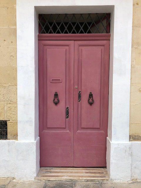large pink door with ornate door knockers